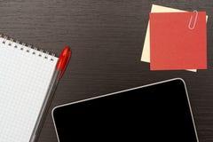 Kontorstabell med minnestavlan, anteckningsboken och pennan Arkivfoto