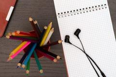 Kontorstabell med minnestavlan, hörlurar, blyertspennor och anteckningsboken Arkivbilder