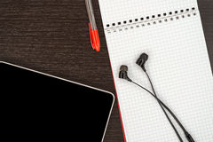 Kontorstabell med minnestavlan, hörlurar, pennan och anteckningsboken Fotografering för Bildbyråer