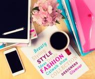 Kontorstabell med modetidskrifter, den digitala minnestavlan, smartphonen och koppen kaffe ovanför sikt Royaltyfri Bild