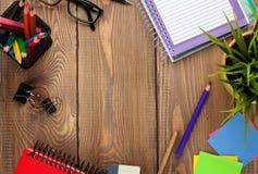 Kontorstabell med notepaden, färgrika blyertspennor, tillförsel och blomman Royaltyfri Foto