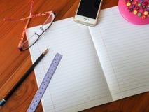 Kontorstabell med notepaden, telefonen och tillförsel Fotografering för Bildbyråer