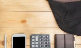 Kontorstabell med pennan, plånboken, räknemaskinen, dräkten och Smart-telefonen Royaltyfria Foton