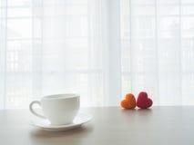 Kontorstabellen med koppen för vitt kaffe och parälsklingen undertecknar nolla Arkivfoto