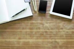 Kontorstabellen med minnestavlan, penna på anteckningsboken, smartphone på gammalt uppvaktar Royaltyfri Fotografi