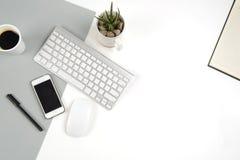 Kontorstabellen med tangentbordet, musen, anteckningsboken och smartphonen på moderna två tonar vit och grå bakgrund Royaltyfria Bilder