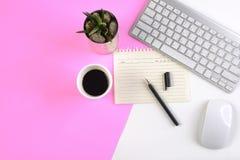 Kontorstabellen med tangentbordet, musen, anteckningsboken och smartphonen på moderna två tonar vit och rosa bakgrund Royaltyfri Bild