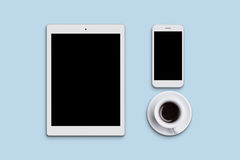 Kontorstabellskrivbord med den moderna minnestavlan, mobiltelefonen och koppen av läckert kaffe eller te Moderna grejer som ligge Royaltyfri Fotografi
