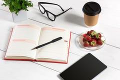 Kontorstabellskrivbord med uppsättningen av tillförsel, tom notepad för vit, kopp, penna, minnestavla, exponeringsglas, blomma på arkivfoton