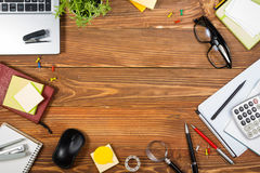Kontorstabellskrivbordet med uppsättningen av färgrika tillförsel, den tomma anteckningsboken för vit, koppen, pennan, PC, skrynk royaltyfria bilder