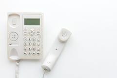 Kontorstelefon på den vita bakgrund, kommunikationen och technoloen Royaltyfria Bilder
