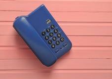Kontorstelefon på en rosa trätabell På form Royaltyfria Bilder