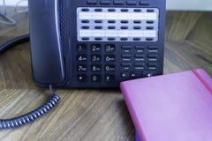 Kontorstelefonkonsol på trätabellen med anteckningsböcker royaltyfri fotografi