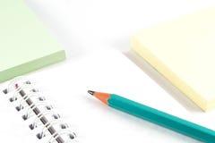 Kontorstillförsel - grafitblyertspenna på den vitt anteckningsboken och färganmärkningspapper Royaltyfria Bilder
