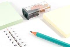 Kontorstillförsel - grafitblyertspenna på den vitt anteckningsboken, pennvässaren och färganmärkningspapper Royaltyfri Bild