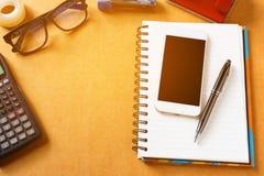 Kontorstillförsel, grejer och ilar telefonen, penna med notepaden på wo royaltyfri bild