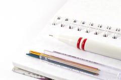 Kontorstillförsel - mekanisk blyertspenna med blyertspennablytak på den vita anteckningsboken Royaltyfria Foton