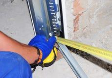 Kontrahent instaluje garażu drzwi z pomiarową taśmą i obraz stock
