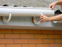 Kontrahent instaluje klingeryt dachową rynnę Plastikowy Guttering Zamienia złotych rączek rękami, Podeszczowy Guttering & drenaż  zdjęcia stock