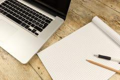 Kontrast między starą i nową biurową pracą: strzał z wierzchu aluminiowego laptopu na drewnianym biurku z otwartym w kratkę notat zdjęcie stock