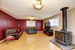 Kontrastera den röda väggen i vardagsrummet med den antika spisen Royaltyfri Bild