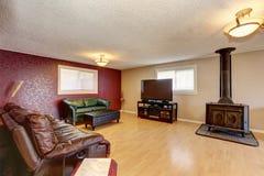 Kontrastera den röda väggen i vardagsrummet med den antika spisen Arkivfoton