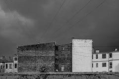 Kontrastieren Sie Schwarzweiss-Backsteinbauten mit Drähten und bewölktem regnerischem und stürmischem Himmel Stockfotografie