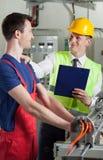 Kontrollant som talar med fabriksarbetaren Royaltyfri Bild