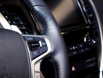 Kontrollbord med knappar på ett svart läderhjul av den moderna bilen Arkivfoto