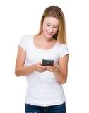 Kontrolle der jungen Frau die Mitteilung auf Mobiltelefon Lizenzfreies Stockfoto