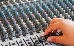 Kontrollen der mischenden Audiokonsole mit der Hand Stockbild