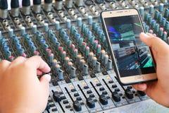 Kontrollen der mischenden Audiokonsole und des Telefons Stockfotografie