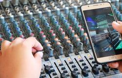 Kontrollen der mischenden Audiokonsole und des Telefons Lizenzfreie Stockfotografie