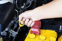 Kontrollera den olje- nivån i en motor royaltyfri foto