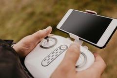 Kontrollera ett avlägset helikoptersurr med smartphoneförtitt royaltyfri bild