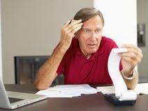 kontrollera finanser home man pensionären Arkivfoton