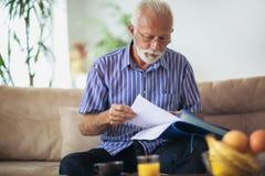 kontrollera finanser home man pensionären arkivbilder