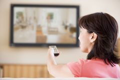 kontrollera fjärrtelevisionen genom att använda den hållande ögonen på kvinnan Arkivfoto