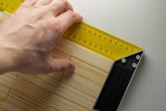 Kontrollera hörnet av tabellen, handen med hörnlinjalen och träkvartertabellen arkivfoto