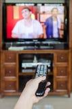 kontrollera handen som rymmer fjärrtv:n Fotografering för Bildbyråer