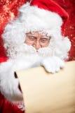 Kontrollera hans traditionella Santa Claus för special lista sammanträde Arkivfoto