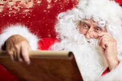 Kontrollera hans traditionella Santa Claus för special lista sammanträde Fotografering för Bildbyråer