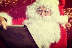 Kontrollera hans traditionella Santa Claus för special lista sammanträde Royaltyfria Foton