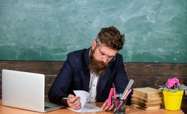 Kontrollera läxa Läraren uppsökte hipsteren med glasögon sitter i svart tavlabakgrund för klassrum Läraren sitter skrivbordet med arkivfoto