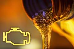 Kontrollera motorlampan och flytandeströmmen av flöden för motorisk olja för motorcykeln från halsen av flasknärbilden Arkivbilder