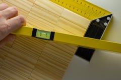 Kontrollera nivån av tabellen, hand med byggnadsnivån eller waterpas och träkvartertabell royaltyfri bild