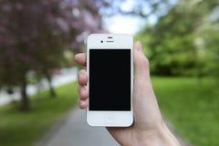 Kontrollera telefonen under att gå på gatan Arkivbild