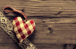 Kontrollerad tyghjärta med snör åt wood bakgrund. Royaltyfri Bild