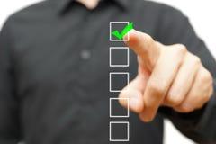 Kontrollerande fläck för ung affärsman på kontrollista med markören Arkivbild