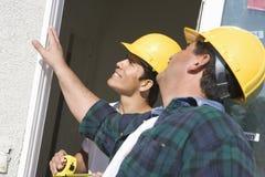 Kontrollerande fönster för byggnadsarbetare Fotografering för Bildbyråer